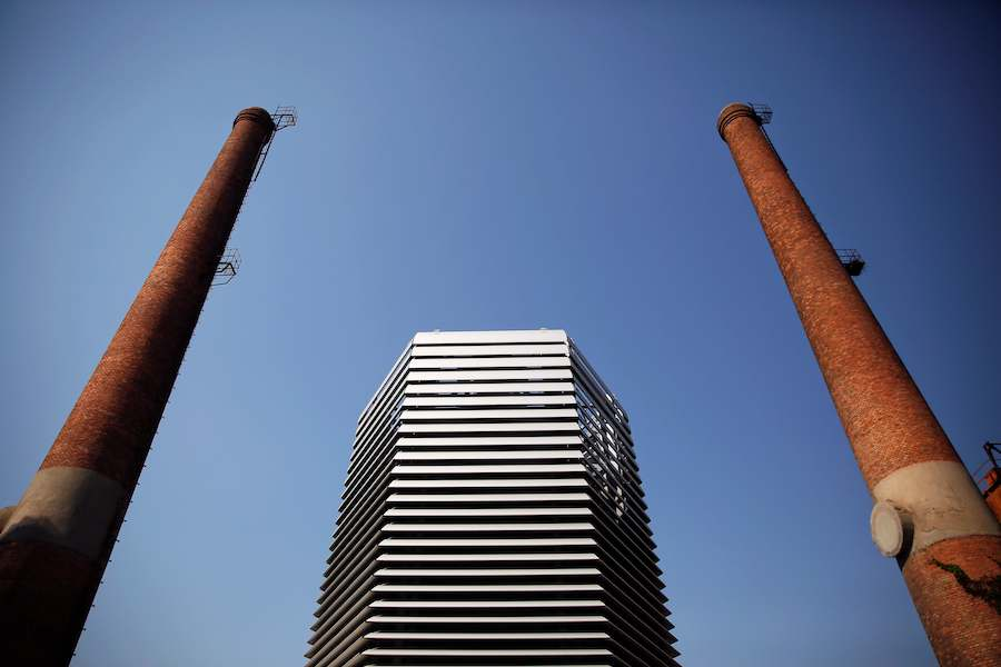 The Smog Free Tower, the world's largest smog vacuum cleaner designed by Dutch artist and innovator Daan Roosegaarde is seen between chimneys as the artist presents his The Smog Free Project at D-751 art zone in Beijing September 29, 2016. The Smog Free Project consist of 7-meter tall the Smog Free Tower, the large air purifier that creates an area of clean air around it and the Smog Free Jewellery that are made of compressed smog particles. REUTERS/Damir Sagolj TPX IMAGES OF THE DAY