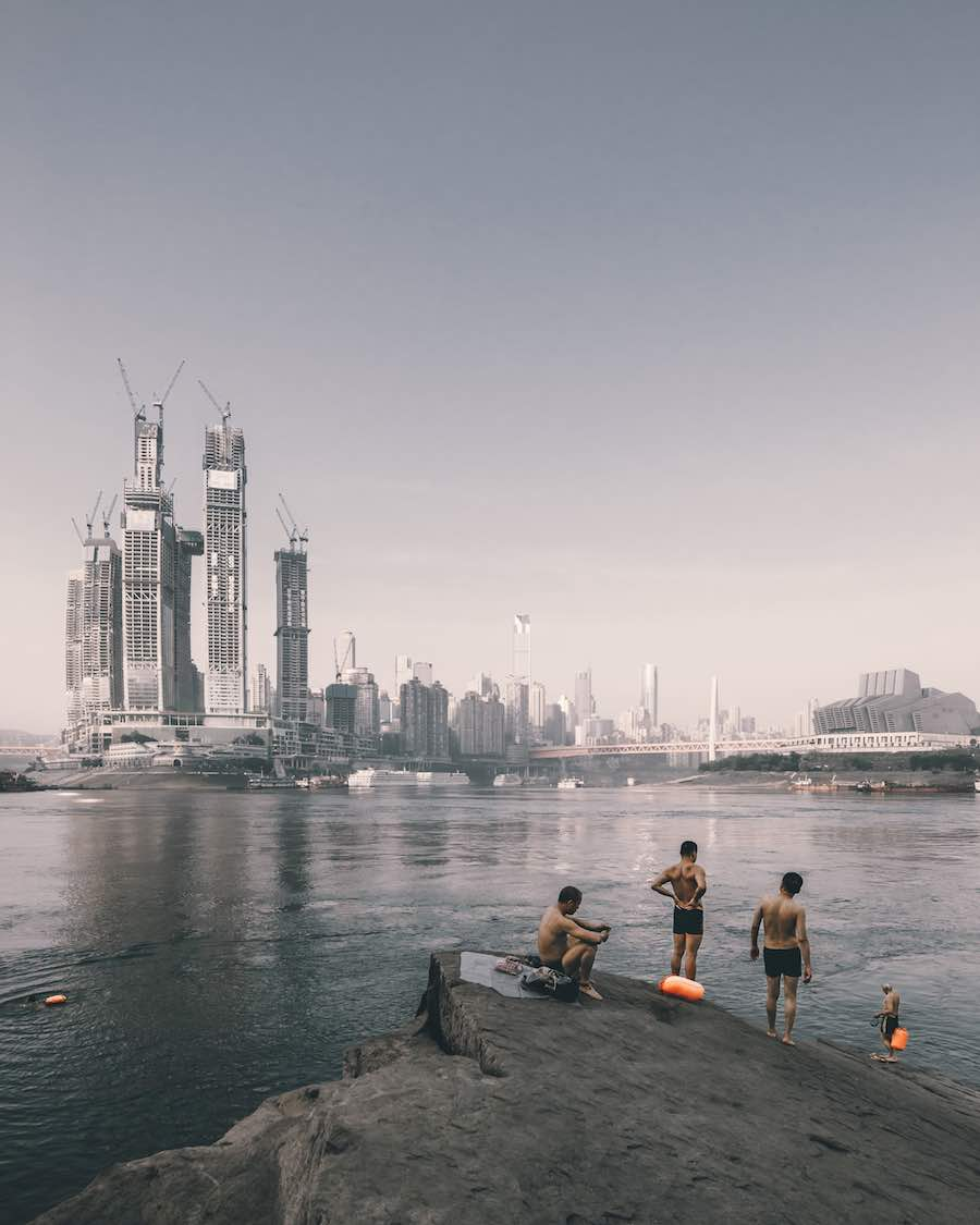 Architectural Photography Awards 2018 - SoP - Swimmers on the riverside opposite the construction of Raffles City Chongqing, China by Sadfie Architects. © Zhu Wenqiao
