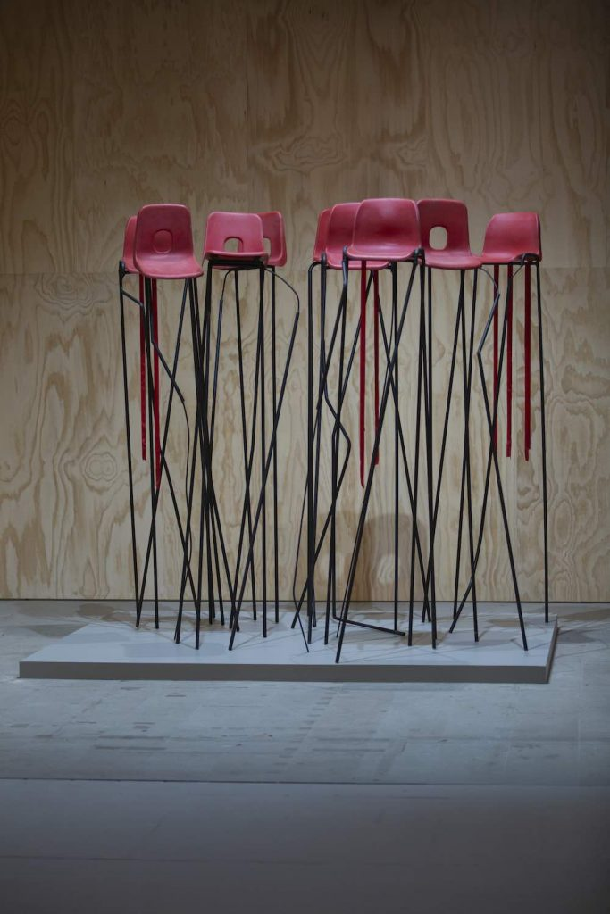 Jesse Darling's installation at Arsenale is a forest of red primary school chairs on spindly, elongated legs. Photo by Italo Rondinella, courtesy of La Biennale di Venezia.